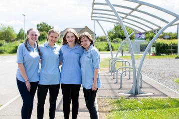 Four young girls stood outside a bike shed