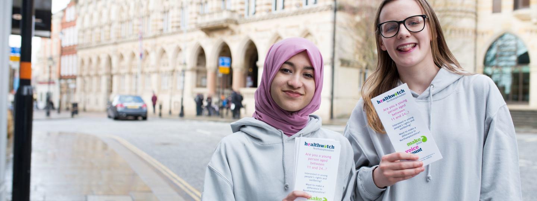 Two women holding healthwatch leaflets